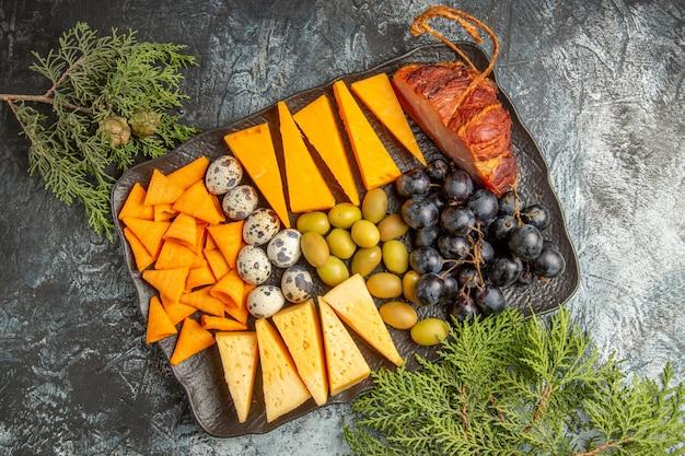 Draufsicht des köstlichen besten snacks für wein auf braunem tablett und tannenzweigen auf eishintergrund