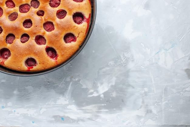 Draufsicht des köstlichen erdbeerkuchens gebacken mit frischen roten erdbeeren innen mit pfanne auf hellweißem schreibtisch, kuchenkeksfrucht süßer teigauflauf