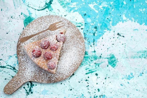 Draufsicht des köstlichen erdbeerkuchens geschnittener köstlicher kuchenzucker, der auf hellblauem süßem backteig des beerenkuchens pulverisiert wird
