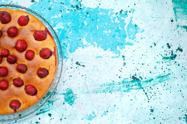 Draufsicht des köstlichen erdbeerkuchens rund geformt mit früchten oben auf hellblauem kuchenteig süßer kekszuckerfruchtbeere