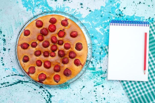 Draufsicht des köstlichen erdbeerkuchens rund geformt mit früchten oben und innen auf blauem kuchenteig süßem keks