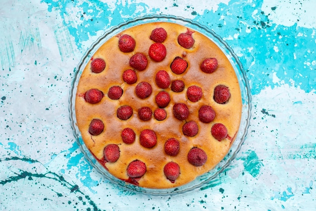Draufsicht des köstlichen erdbeerkuchens rund geformt mit früchten oben und innen auf hellblauem schreibtisch, kuchenteig süßer kekszucker