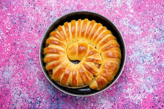 Draufsicht des köstlichen gebackenen gebäckarmreifs gebildet innerhalb der pfanne auf hellem schreibtisch, süßer zucker des gebäckkekskekses