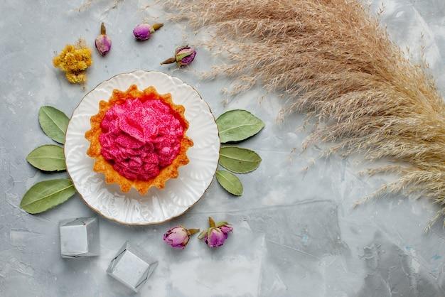 Draufsicht des köstlichen gebackenen kuchens mit rosa sahne und pralinen auf leichtem kuchen-keks-süßem backcremetee