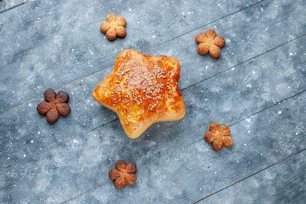 Draufsicht des köstlichen gebäcksterns geformt mit plätzchen auf grauem schreibtisch, süßes backgebäckzuckerkuchen