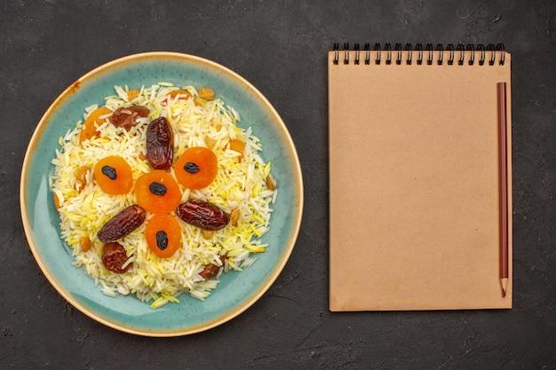 Draufsicht des köstlichen gekochten plov-reises mit verschiedenen rosinen innerhalb der platte auf dunkelgrauer oberfläche