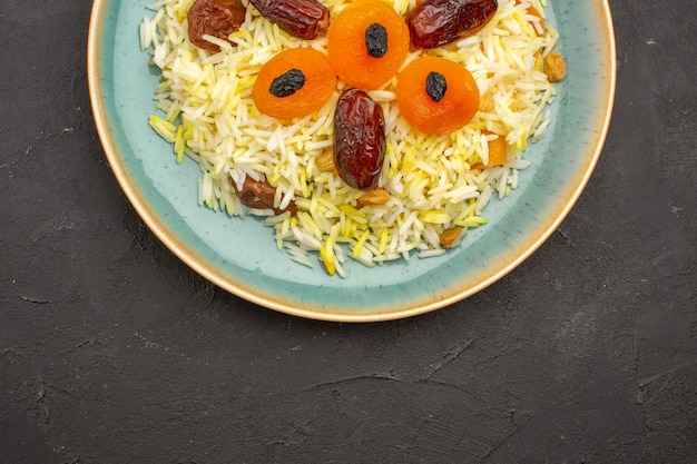 Draufsicht des köstlichen gekochten plov-reises mit verschiedenen rosinen innerhalb platte auf der grauen oberfläche