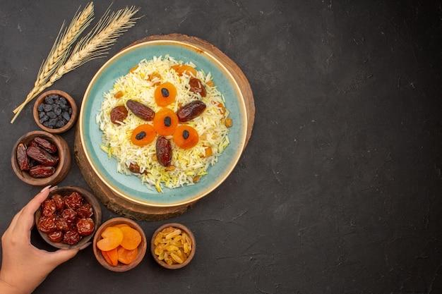Draufsicht des köstlichen gekochten plov-reises mit verschiedenen rosinen innerhalb platte auf dunkler oberfläche