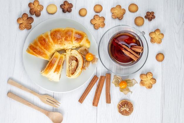 Draufsicht des köstlichen geschnittenen gebäcks innerhalb der platte mit füllung zusammen mit tee und keksen auf weißem schreibtisch, gebäckkekskeks süß