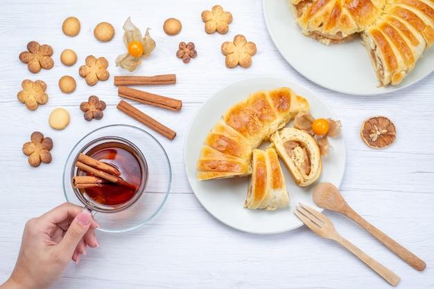 Draufsicht des köstlichen geschnittenen gebäcks innerhalb der platte mit füllung zusammen mit teezimt und keksen auf leichtem gebäckkekskeks süß