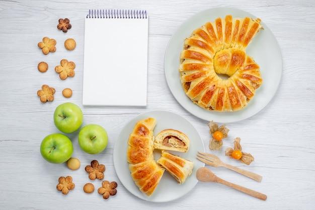Draufsicht des köstlichen geschnittenen gebäcks innerhalb des tellers mit füllung zusammen mit grünem apfelnotizblock und keksen auf weißem schreibtisch, gebäckkekskeks süß