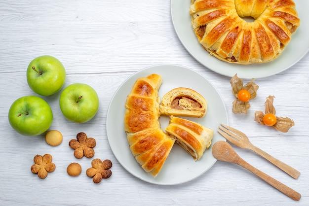 Draufsicht des köstlichen geschnittenen gebäcks innerhalb des tellers mit füllung zusammen mit grünen äpfeln und keksen auf weißem, süßem zucker des gebäckkekskekses