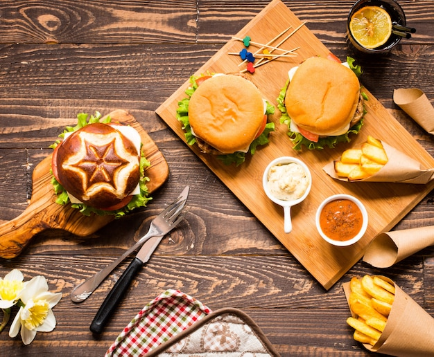 Draufsicht des köstlichen hamburgers mit gemüse auf einem hölzernen hintergrund.