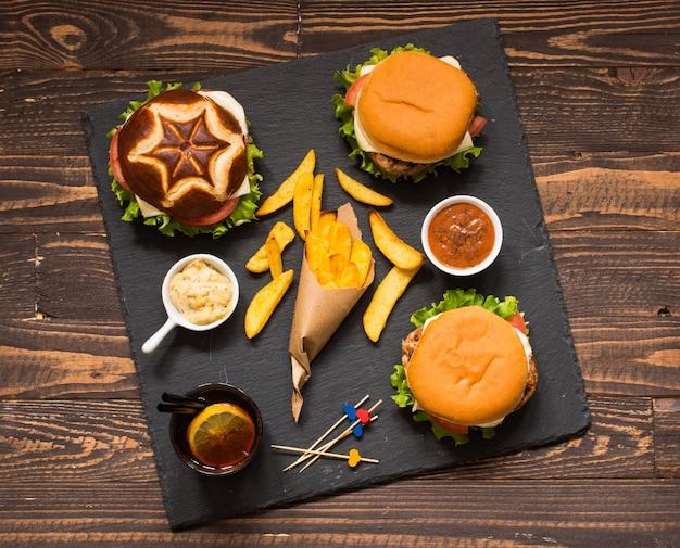Draufsicht des köstlichen hamburgers, mit gemüse, auf einem hölzernen hintergrund.
