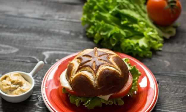 Draufsicht des köstlichen hamburgers, mit gemüse, auf einem holztisch
