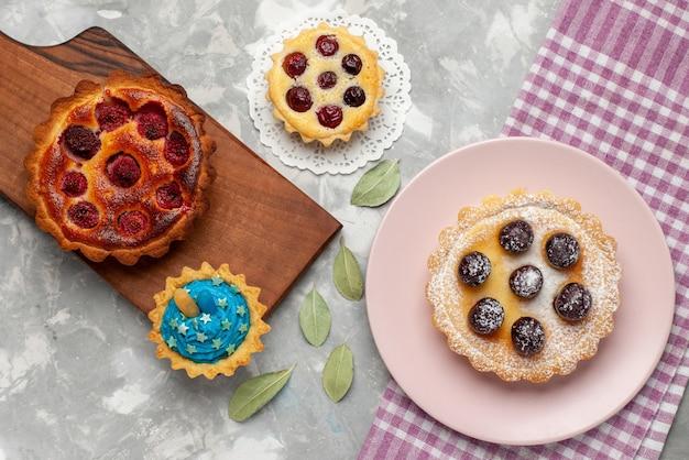 Draufsicht des köstlichen himbeerkuchens mit kleinen kuchen auf hellem schreibtisch, kuchenfrucht-beeren-torte