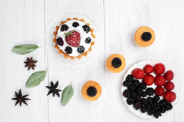 Draufsicht des köstlichen kleinen kuchens mit sahne- und beerenplätzchen auf der weißen beere des weißen kuchenkeks backen frucht