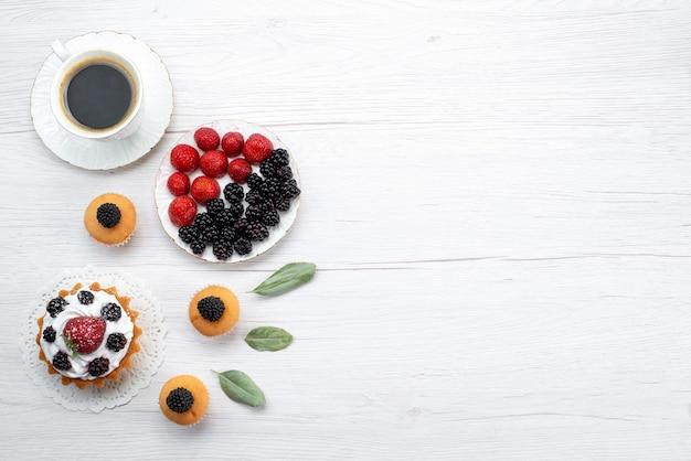 Draufsicht des köstlichen kleinen kuchens mit sahne- und beerenplätzchen auf weißem schreibtisch, kuchenkeks backen fruchtbeere