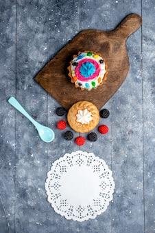 Draufsicht des köstlichen kuchens mit sahne und bonbons zusammen mit beerenplätzchenkuchen auf hellem schreibtisch, kuchenkeks süßes backbonbon