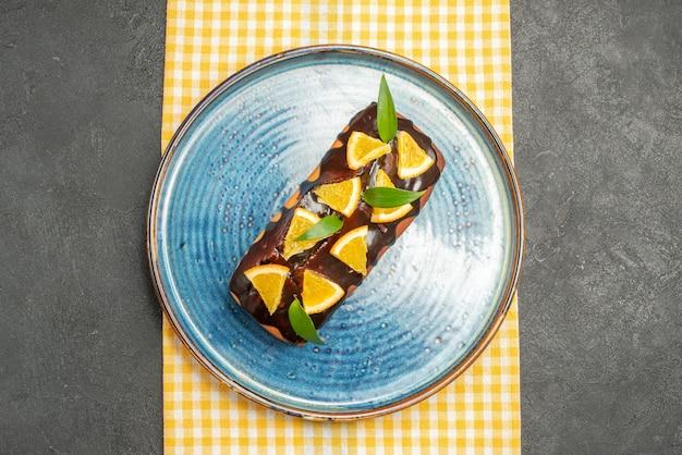 Draufsicht des köstlichen kuchens verziert mit zitrone und schokolade auf gelbem gestreiftem handtuch