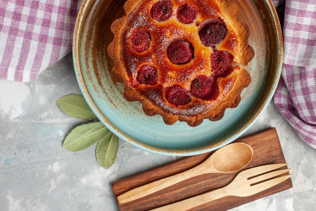 Draufsicht des köstlichen obstkuchens mit gebackenen himbeeren innen auf leichtem süßem tee des kuchenbackens