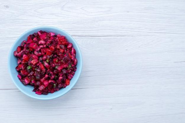 Draufsicht des köstlichen rübensalats, der mit gemüse und gemüse in blauer platte auf leichtem, pflanzlichem vitamin-lebensmittelmahlzeit-gesundheitssalat geschnitten wird