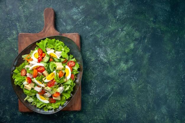 Draufsicht des köstlichen salats mit vielen frischen bestandteilen auf der rechten seite auf hölzernem schneidebrett auf schwarzgrünem mischfarbenhintergrund