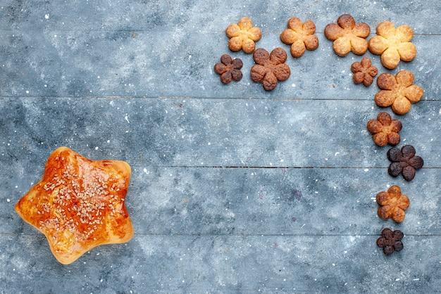 Draufsicht des köstlichen süßen gebäcksterns geformt mit plätzchen auf grauem schreibtisch, süßes backgebäckkuchen