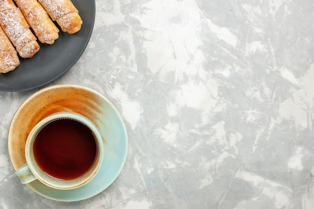 Draufsicht des köstlichen teigs des zuckerpulver-bagels mit tasse tee auf weißer oberfläche