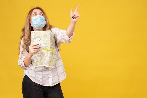 Draufsicht des konzentrierten reisenden mädchens, das ihre maske und den rucksack hält karte hält, die auf gelb zeigt