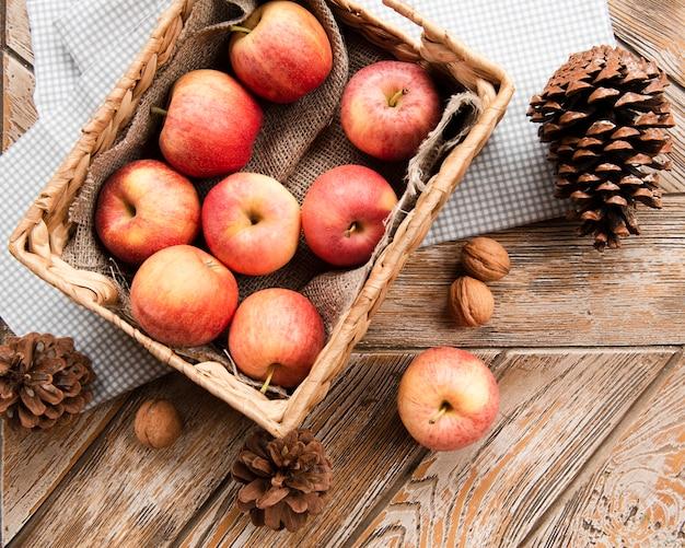 Draufsicht des korbes der äpfel mit kiefernkegeln