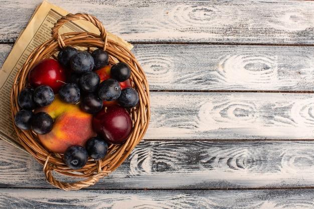Draufsicht des korbes mit früchten auf dem grauen hölzernen des