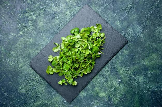 Draufsicht des korianderbündels auf hölzernem schneidebrett auf grünem schwarzem mischfarbenhintergrund mit freiem raum