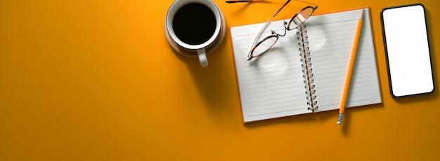Draufsicht des kreativen arbeitstisches mit leerem bildschirm-smartphone, tagebuchnotizbuch, kaffeetasse, brille und kopierraum