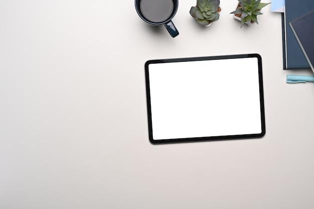 Draufsicht des kreativen designerarbeitsbereichs mit digitalem tablett, kaffeetasse, notizbuch und pflanze auf weißem tisch.