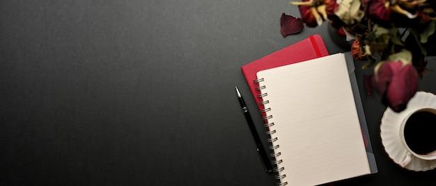 Draufsicht des kreativen flachen arbeitsbereichs mit notizbüchern, getrockneten rosen, kaffeetasse und kopierraum auf schwarzem tisch