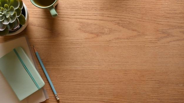 Draufsicht des kreativen flachen hölzernen arbeitsbereichs mit schreibwarenplatbecher und kopierraum