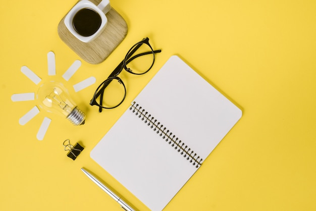 Draufsicht des kreativen flachen lagekonzeptes des arbeitsplatzschreibtischs redete designbüroartikel mit stift, notizblock, brillen an
