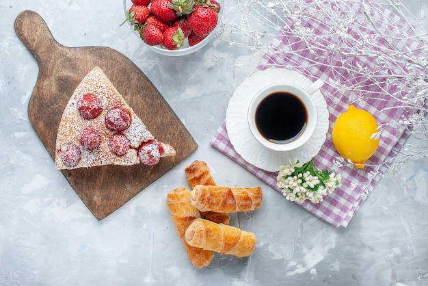 Draufsicht des kuchenstücks mit süßen armreifen der frischen roten erdbeeren und kaffee auf hellem schreibtisch, süßes backkeksplätzchen-teegebäck