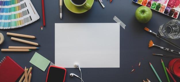 Draufsicht des künstlerstudios mit skizzenpapier, malwerkzeugen, wasserfarben und büroartikeln