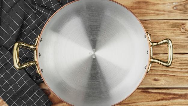 Draufsicht des kupfernen kochenden topfes auf küchentisch