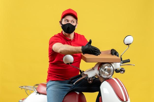 Draufsicht des kuriermannes, der rote bluse und huthandschuhe in der medizinischen maske trägt, die auf roller sitzt, der befehl zeigt, jemanden willkommen zu heißen