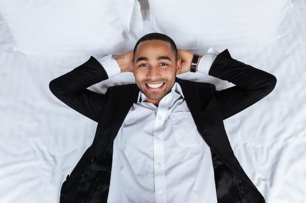 Draufsicht des lächelnden afrikanischen mannes, der auf bett im hotelzimmer liegt