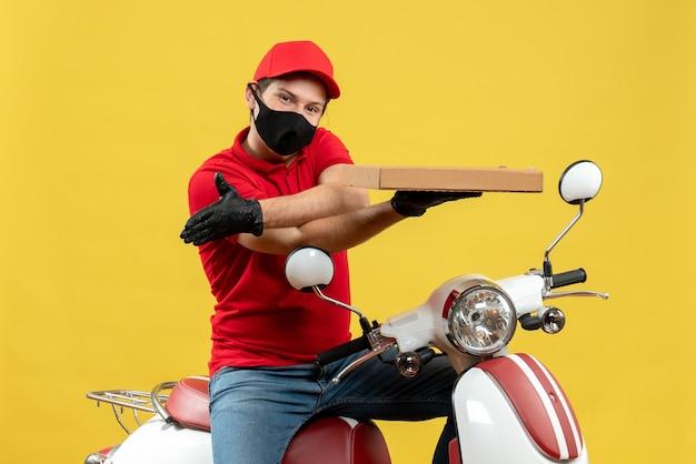 Draufsicht des lächelnden kuriermannes, der rote bluse und huthandschuhe in der medizinischen maske trägt, die auf roller sitzt, zeigt befehl, jemanden willkommen zu heißen