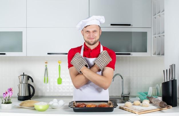 Draufsicht des lächelnden männlichen kochs, der einen halter trägt, der hinter dem tisch mit gebäck-eierreibe darauf steht und in der weißen küche eine stopp-geste macht