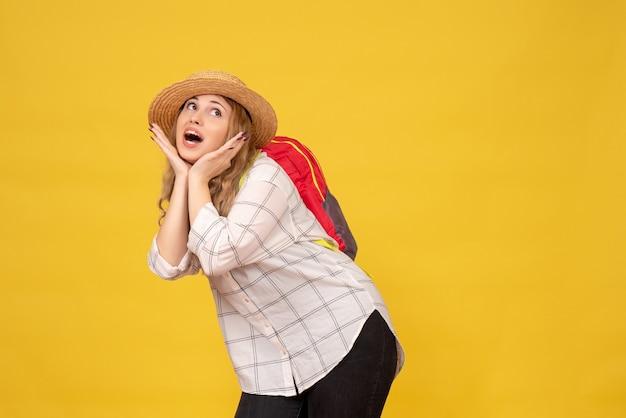 Draufsicht des lächelnden reisenden mädchens, das ihren hut und roten rucksack trägt, der für kamera auf gelb aufwirft