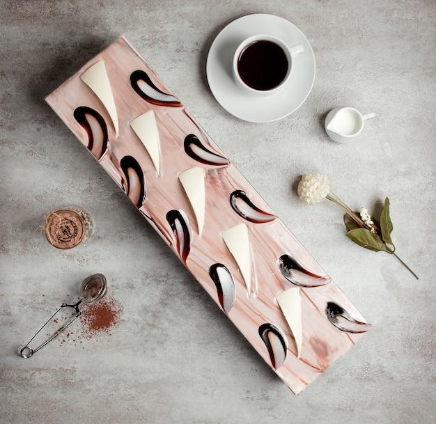 Draufsicht des langen kuchens verziert mit kaffeesirup und weißer schokolade