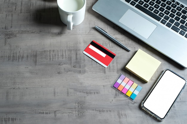 Draufsicht des laptops, des smartphone, der kreditkarte, der schale milch, der papieranmerkung, des stiftes, auf holztisch mit geschäft, handel, finanzierung, bildungskonzept und design