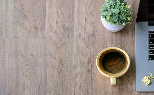 Draufsicht des laptops, des tasse kaffees und der zimmerpflanze auf holztisch.