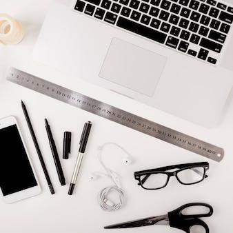 Draufsicht des laptops; handy und schreibwaren auf weißem hintergrund